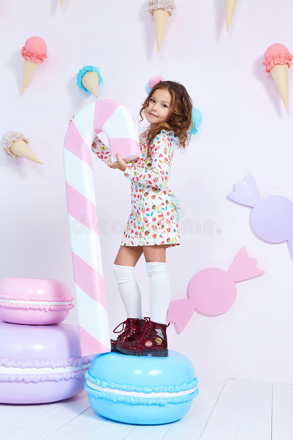 Cute little baby girl fashion pretty model dark blonde curly. Lady hair funny child birthday party fun children room candy bar sweet ice cream play with toy stock photos