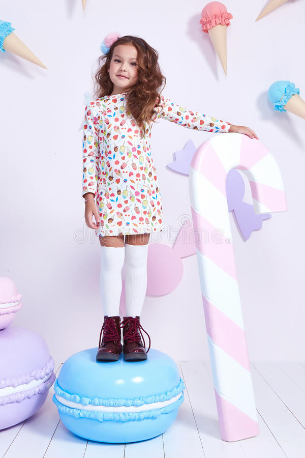 Cute little baby girl fashion pretty model dark blonde curly. Lady hair funny child birthday party fun children room candy bar sweet ice cream play with toy royalty free stock photography