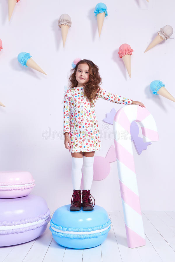 Cute little baby girl fashion pretty model dark blonde curly. Lady hair funny child birthday party fun children room candy bar sweet ice cream play with toy royalty free stock images