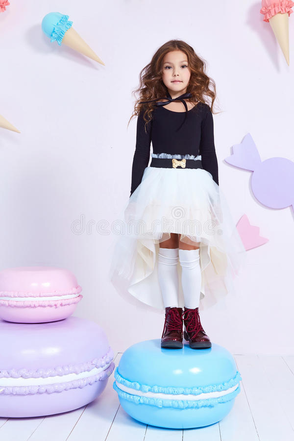 Cute little baby girl fashion pretty model dark blonde curly. Lady hair funny child birthday party fun children room decoration candy bar sweet play toy wear royalty free stock photography