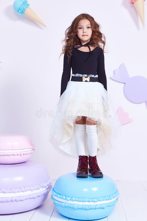 Cute little baby girl fashion pretty model dark blonde curly. Lady hair funny child birthday party fun children room decoration candy bar sweet play toy wear stock images