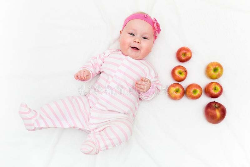 Cute little baby girl laying on white background with fresh red-green apples in shape of number four stock photo