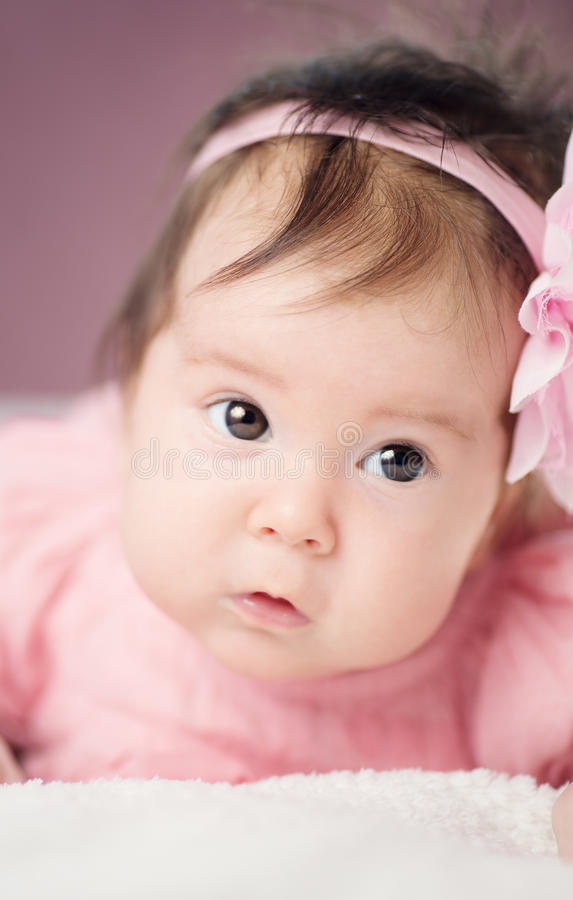 Cute little baby girl lying in the bed in pink dress royalty free stock photo