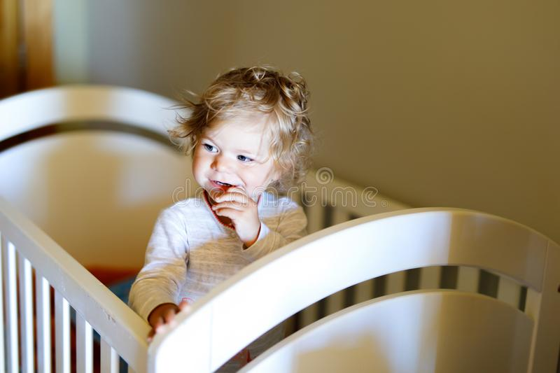 Cute little baby girl lying in cot after sleeping. Healthy happy child in bed climbing out. Danger for babies and children royalty free stock photography