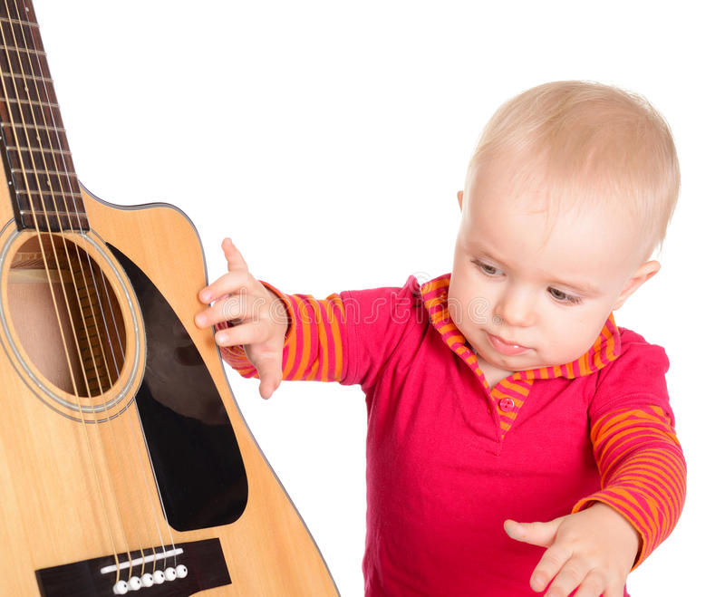 Cute little baby musician playing guitar isolated on white background. royalty free stock images