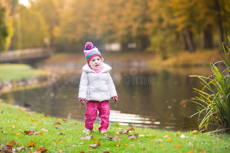 Cute little baby girl next to river in autumn park stock images