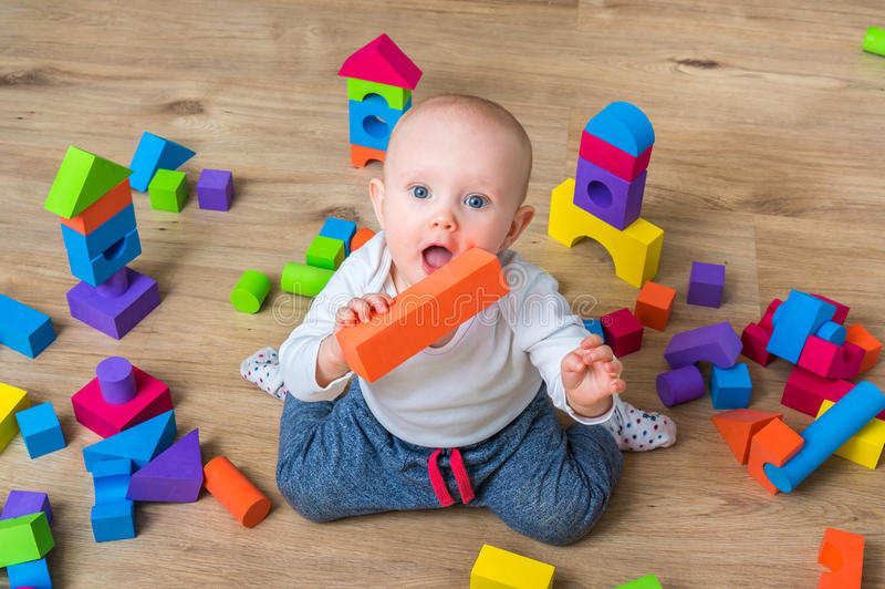 Cute little baby girl playing with colorful toy blocks royalty free stock photography