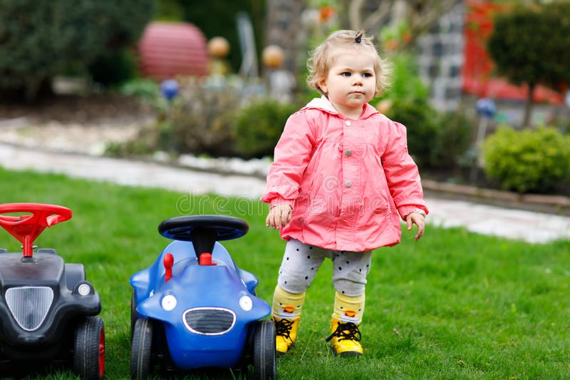 Cute little baby girl playing with two toy cars in garden. Adorable toddler child having fun. Girl in colorful fashion. Clothes. Spring and summertime, active royalty free stock photos