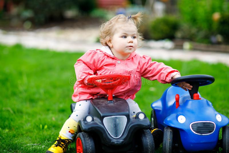 Cute little baby girl playing with two toy cars in garden. Adorable toddler child having fun. Girl in colorful fashion. Clothes. Spring and summertime, active royalty free stock photography