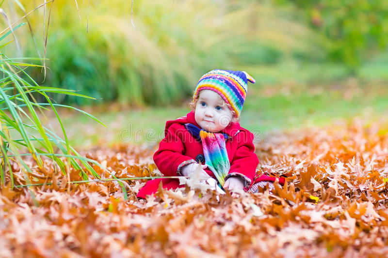 Cute Little Baby Girl In A Red Coat In Autumn Park Stock Photo