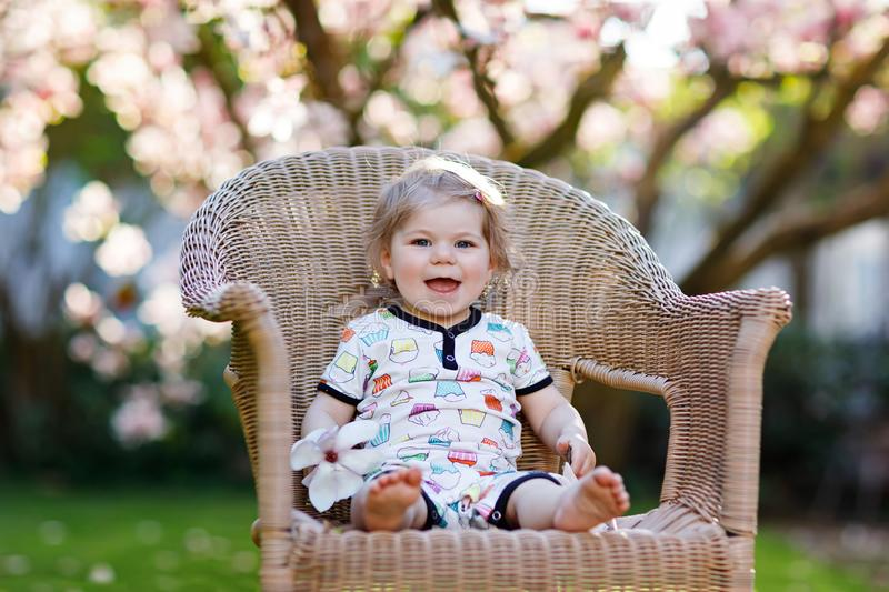 Cute little baby girl sitting on big chair in garden. Beautiful happy smiling toddler with blooming pink magnolia tree royalty free stock photos