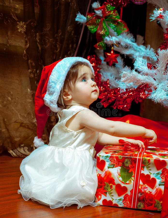Cute little baby girl in Stana hat opens her first Christmas present royalty free stock photography