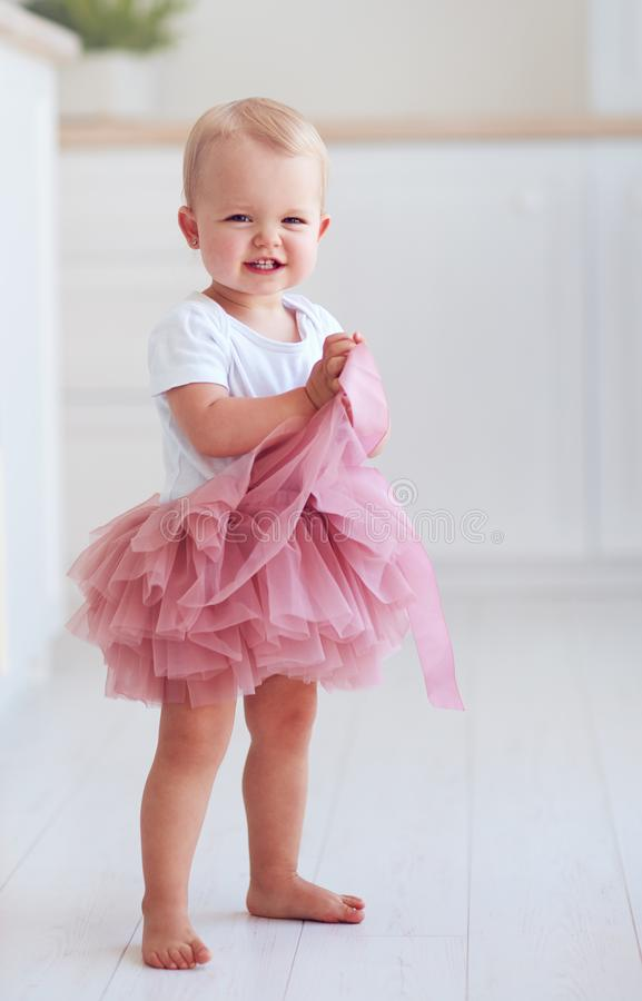 Cute little baby girl in tutu skirt stands on the floor at home royalty free stock photography