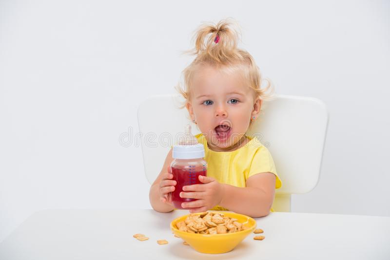 Cute little baby girl 1 year old eating cereal flakes and drinking juice or compote from a bottle at the table isolated on white. Background royalty free stock photography