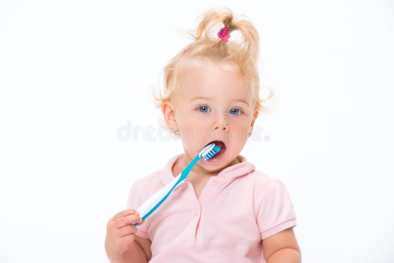 Cute little baby girl 1 year old in pink t-shirt brushing her teeth isolated on white background royalty free stock images