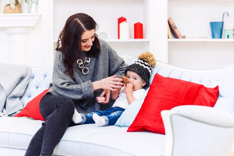 Cute baby having fun with her mother on the comfortable blue sofa in the festive decorated christmas room. Happy winter stock photo