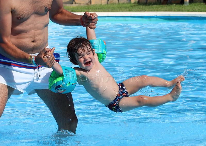 Cute little baby on inflatable sleeves playing with his father in a swimming pool during a hot summer morning royalty free stock photography