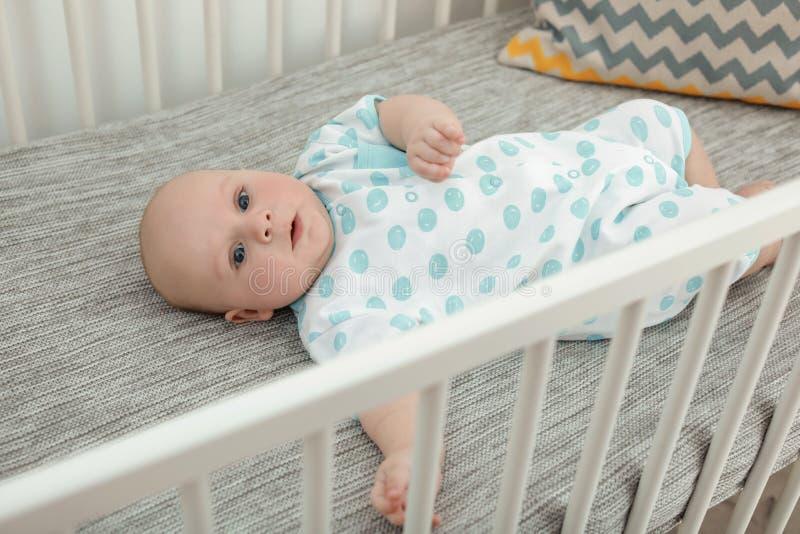 Little baby lying in comfortable crib. Cute little baby lying in comfortable crib stock images