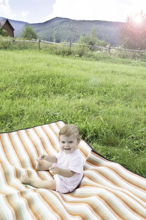 Cute little baby on the meadow in summer day royalty free stock photos