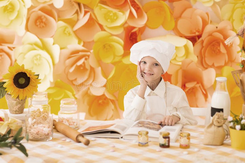 Cute little baby is preparing tasty meals in the kitchen royalty free stock photography