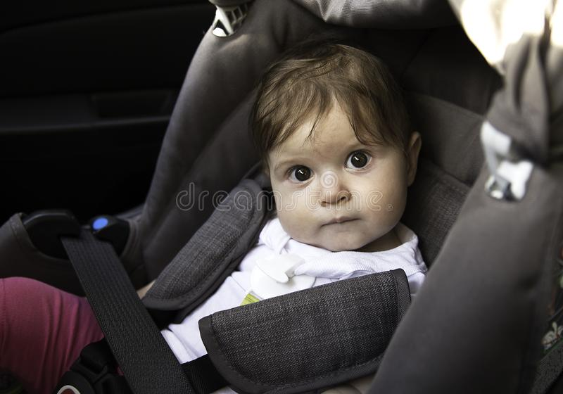 Cute little baby sits fastened in a car seat ready for a ride. Child safety concept. Adorable little baby sitting in car fastened and ready to ride with parents stock images