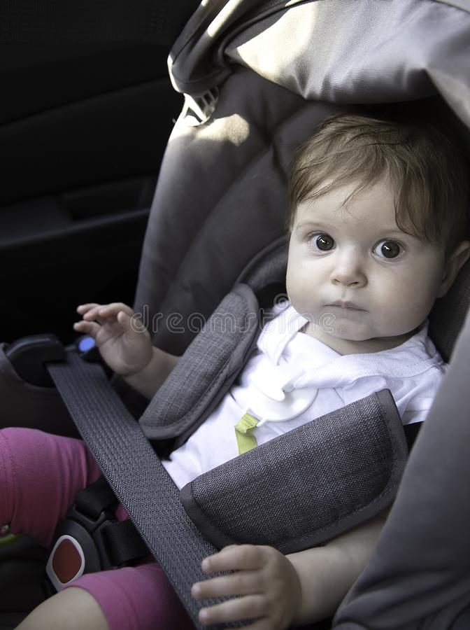Cute little baby sits fastened in a child car seat ready for a ride. Child safety concept. Cute little baby sits fastened in a child car seat ready for a ride stock image