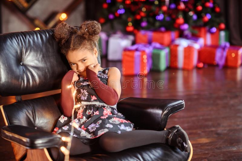 Beautiful kid girl 5-6 year old wearing stylish dress sitting in armchair over Christmas tree in room. Looking at camera. Holiday royalty free stock photo