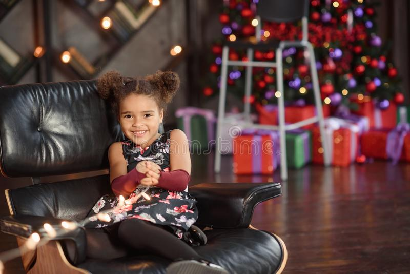 Beautiful kid girl 5-6 year old wearing stylish dress sitting in armchair over Christmas tree in room. Looking at camera. Holiday stock photography