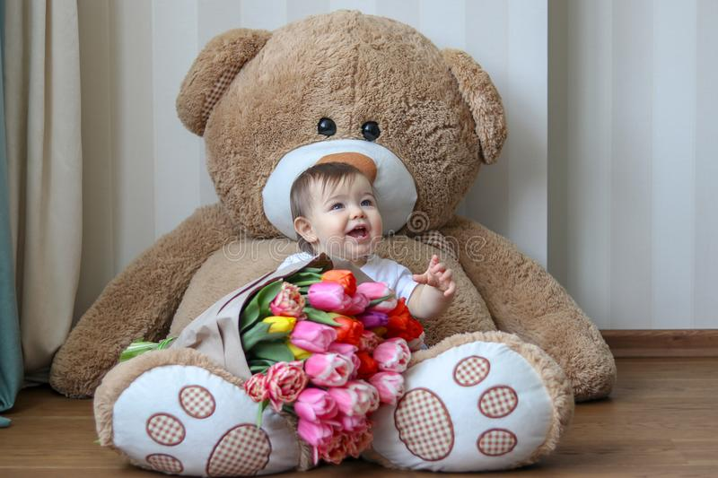 Cute little baby smiling with his first teeth, sitting on huge teddy bear with big bouquet of tulips stock photos