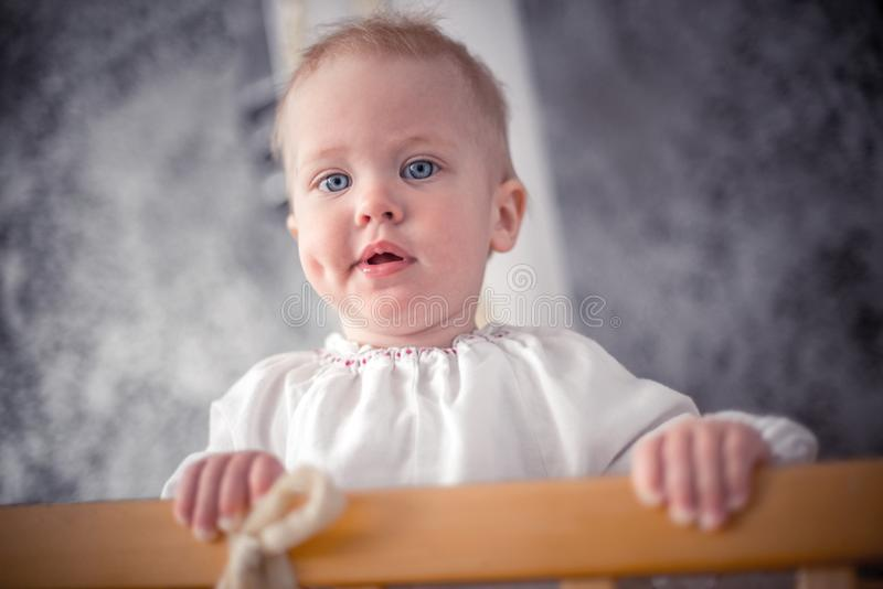 Cute little baby standing in crib. At home stock photo