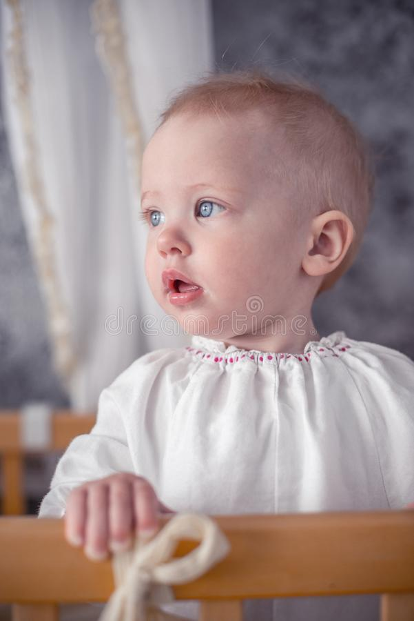 Cute little baby standing in crib at home. Cute little baby standing in wooden crib at home stock photo