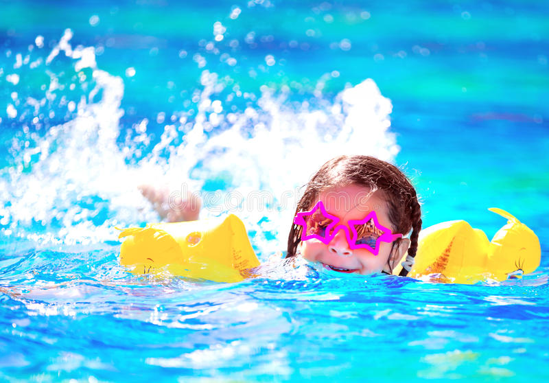 Cute little baby swiming in the pool. Wearing funny sunglasses, enjoying summer weekend in aquapark, holidays and vacation concept stock photo