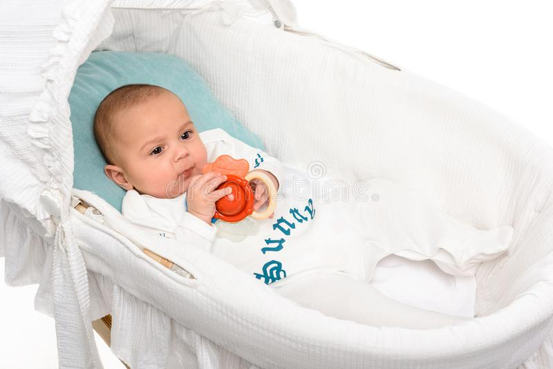 Cute little baby with toy lying in crib. Isolated on white stock photography