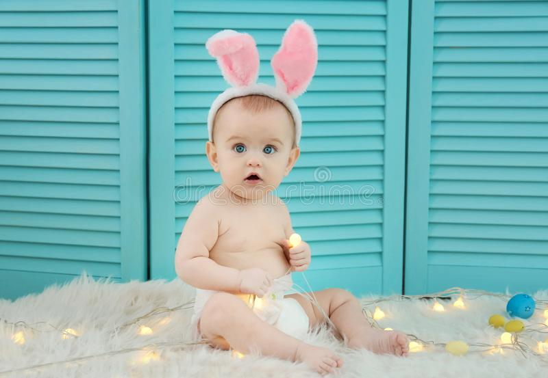 Cute little baby wearing bunny ears sitting on furry rug stock photos