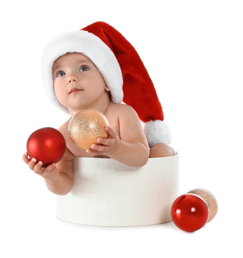 Cute little baby wearing Santa hat sitting in box with Christmas decorations on white royalty free stock photography