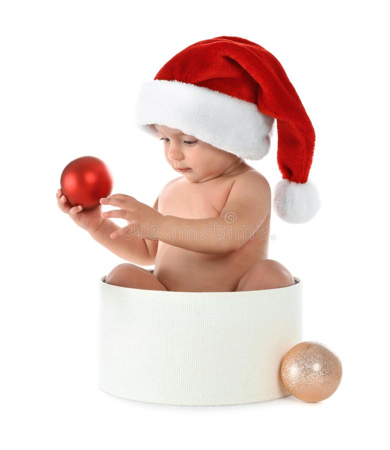 Cute little baby wearing Santa hat sitting in box with Christmas decorations on white stock image