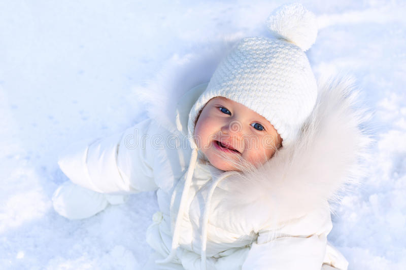 Cute little baby in a white jacket and white hat sitting in fresh winter snow royalty free stock images