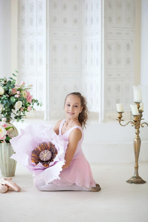 A cute little ballerina in a ballet costume is sitting on the floor with a big flower and smiling. Girl in the dance class. The gi stock photos