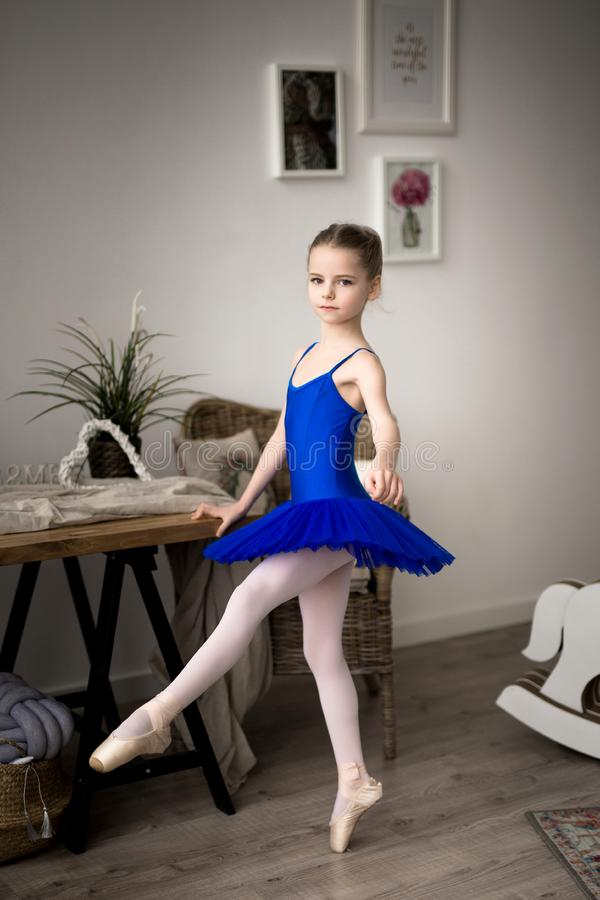Cute little ballerina in blue ballet costume and pointe shoes royalty free stock images