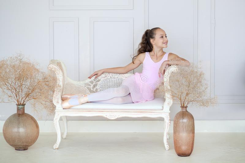 A cute little ballerina in a pink ballet costume and pointe sits on the sofa. Ballerina in the dance class. The girl is studying b. Allet. Ballerina dancing in a royalty free stock photo