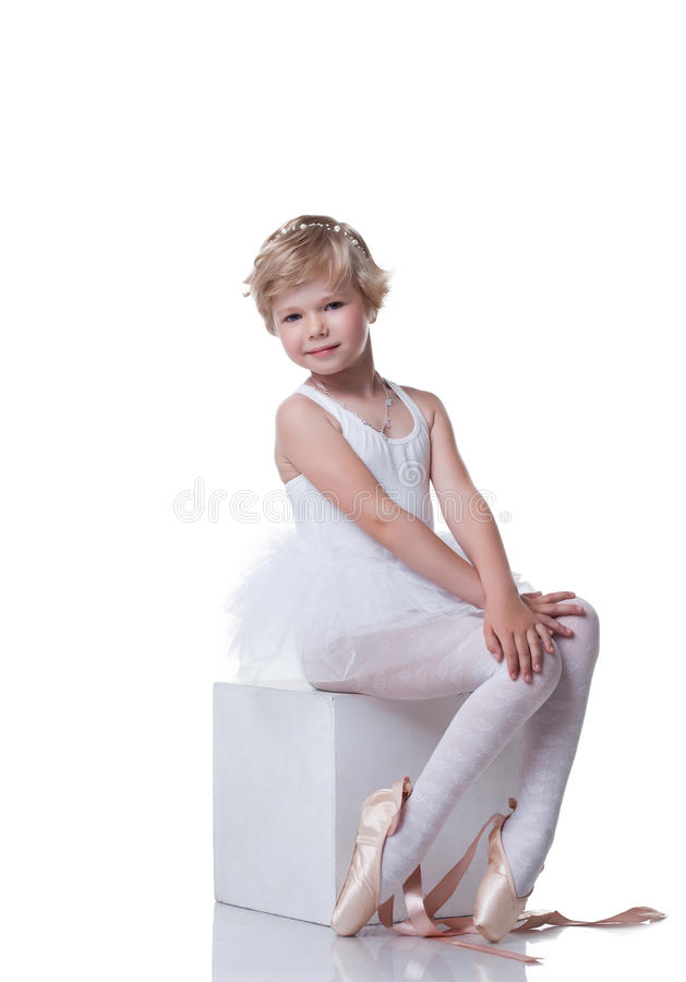 Cute little ballerina sitting on cube in studio. Cute little ballerina sitting on cube, isolated over white background stock images