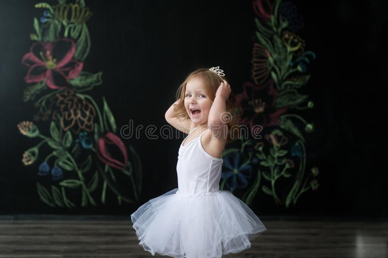 Cute little ballerina in white ballet costume is dancing in the room. Kid in dance class. royalty free stock images