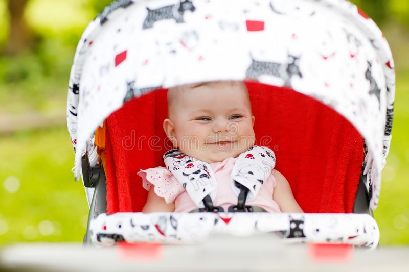 Cute little beautiful baby girl of 6 months sitting in the pram or stroller and waiting for mom royalty free stock images