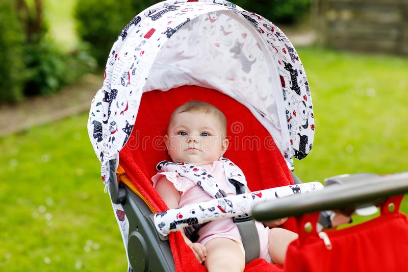 Cute little beautiful baby girl of 6 months sitting in the pram or stroller and waiting for mom royalty free stock image