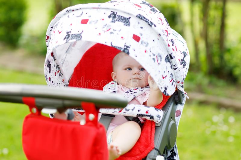 Cute little beautiful baby girl of 6 months sitting in the pram or stroller and waiting for mom royalty free stock photo