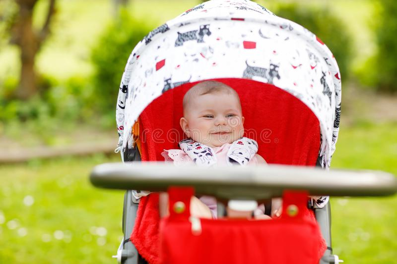 Cute little beautiful baby girl of 6 months sitting in the pram or stroller and waiting for mom stock images