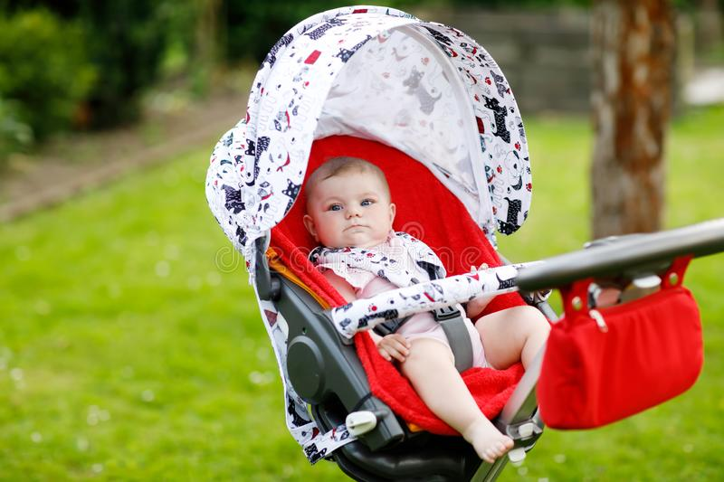 Cute little beautiful baby girl of 6 months sitting in the pram or stroller and waiting for mom. Happy smiling child. With blue eyes stock photos