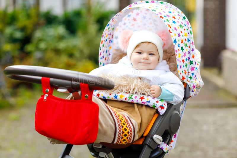 Cute little beautiful baby girl sitting in the pram or stroller on autumn day. Happy healthy child going for a walk on. Fresh air in warm clothes. Baby with in stock photos