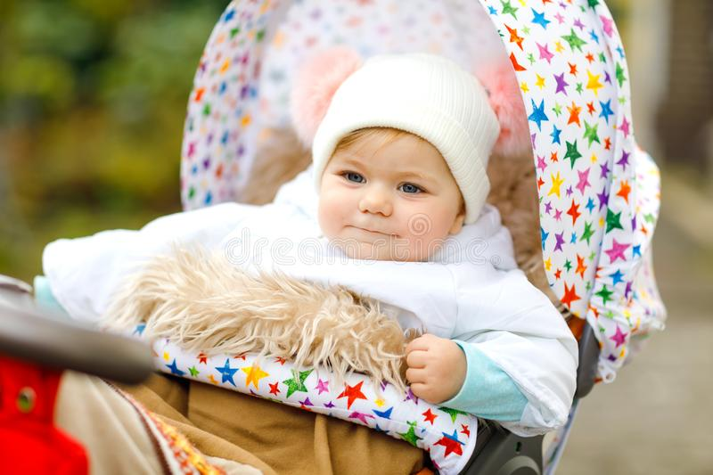 Cute little beautiful baby girl sitting in the pram or stroller on autumn day. Happy healthy child going for a walk on. Fresh air in warm clothes. Baby with in stock images