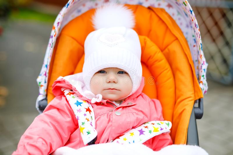 Cute little beautiful baby girl sitting in the pram or stroller on autumn day. Happy healthy child going for a walk on. Fresh air in warm clothes. Baby with royalty free stock photography